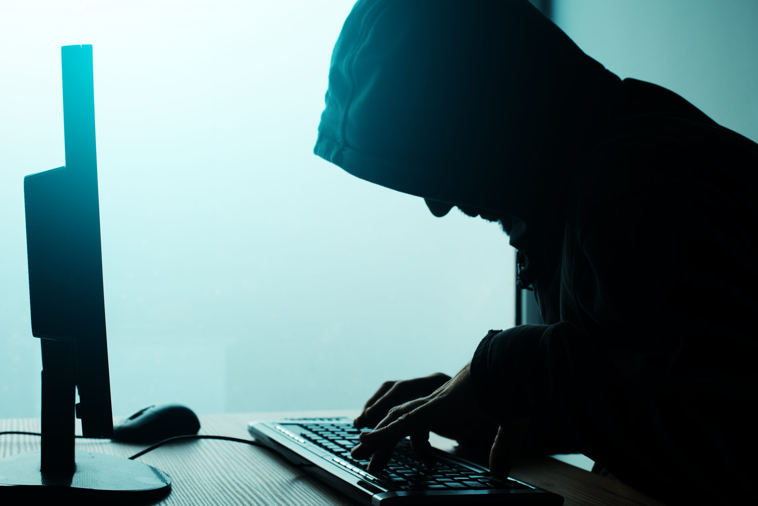 hooded-computer-hacker-hacking-network-P2V3SQY